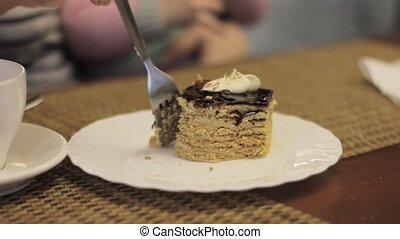 Woman eating a beautiful, appetizing piece cake at cafe....