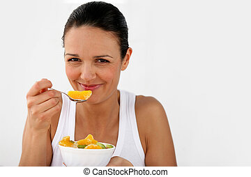 Woman eating a bowl of fruit