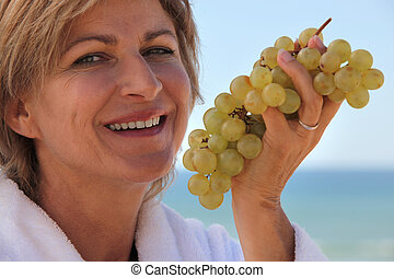 Woman eating a bunch of grapes