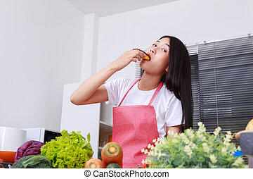 woman eating a chocolate donut in kitchen room