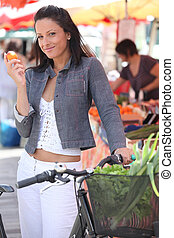 Woman eating a clementine while standing with her bike at a market
