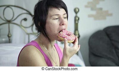 woman eating a donut on a bed, breakfast with junk food.