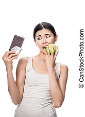 Woman eating a fresh apple while looking at chocolate