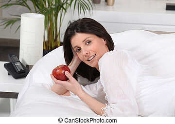 Woman eating a red apple in bed
