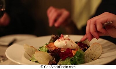 Woman eating a salad in a restaurant close up
