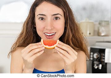 Woman eating a slice of fruit