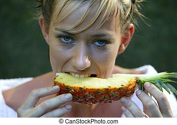 Woman eating a slice of pineapple