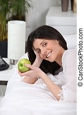 Woman eating an apple on her coach
