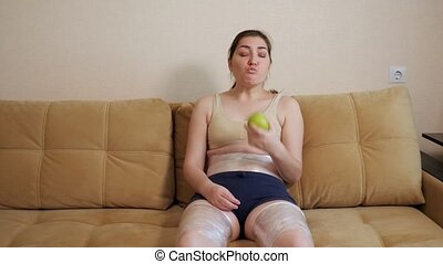 Woman eating an apple sitting on the couch. Thighs and belly wrapped in plastic wrap