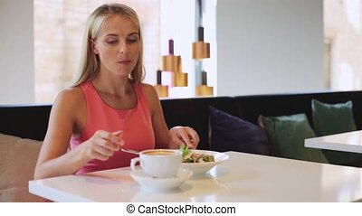woman eating and drinking coffee at restaurant