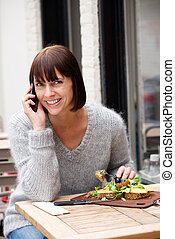 Woman eating and smiling with mobile phone