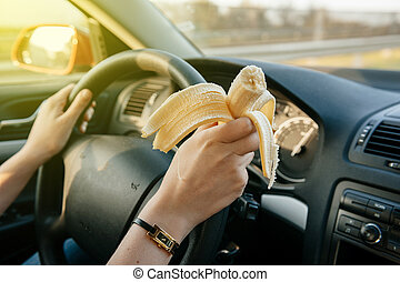 Woman eating banana while driving on highway - Woman eating...
