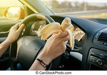 Woman eating banana while driving on highway - Woman eating...