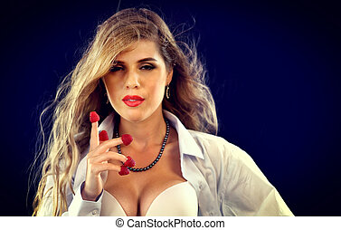 Woman eating berry. Pin up girl wearing unbuttoned blouse...