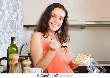 Woman eating biscuit in kitchen
