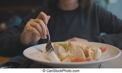 Woman eating caesar salad in a cafe