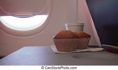 Woman eating cake and drinks a drink from paper cup at the table flying plane stock footage video