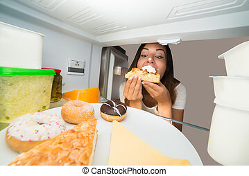 Woman Eating Cake In Refrigerator