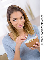 Woman eating cereal for breakfast