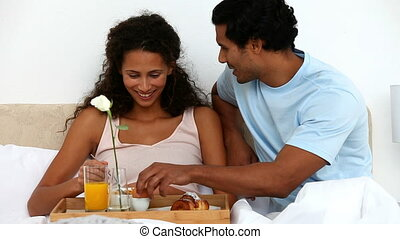 Woman eating cereals for breakfast with her husband