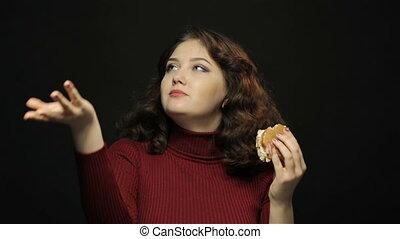 Woman eating cheeseburger, closeup shooting