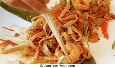 Woman eating Chinese seafood with shrimp and noodles using...
