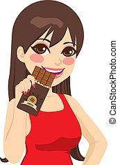 Woman Eating Chocolate Bar - Beautiful brunette woman eating...
