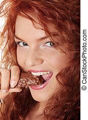 Woman eating chocolate bar