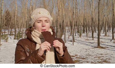 Woman eating chocolate outdoors