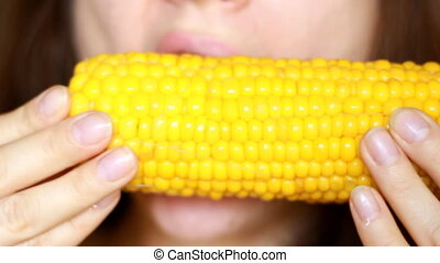 Woman eating corn closeup. Vegetarian food vegetable.