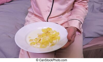 Woman eating cornflakes with milk in the bed