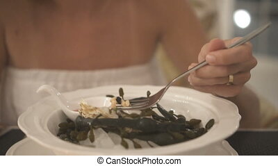Woman eating delicious oyster meal appetizer in restaurant -...