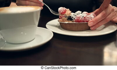 Woman eating dessert and drinking coffee in a cafe, close-up