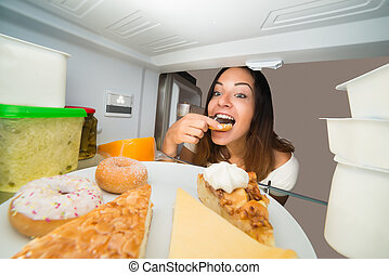 Woman Eating Donut From Refrigerator