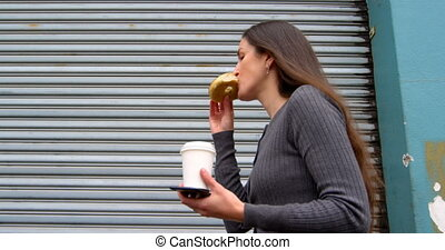 Woman eating donuts while walking on street 4k