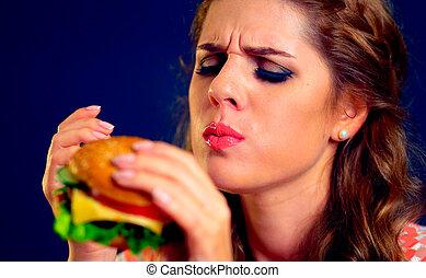 Woman eating fast food. Girl enjoying delicious hamburger.