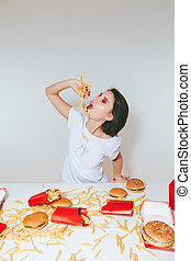 Woman eating french fries at the table with fast food