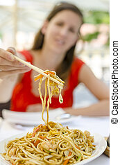 Woman eating fried noodles