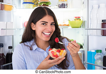 Woman Eating Fruits In Bowl