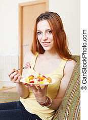 woman eating fruits salad