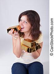 Woman eating gold bars