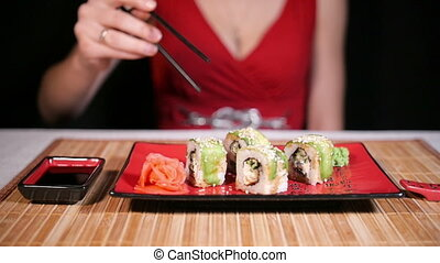 Woman Eating Green Sushi Rolls - Woman in red dress eating...