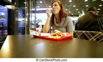 Woman eating hamburger, french fries in fast food