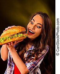 Woman eating hamburger. Girl bite of very big burger - Woman...