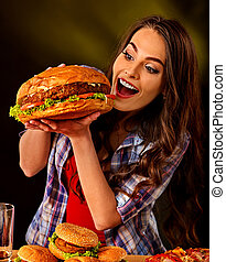 Woman eating hamburger. Girl bite of very big burger - Woman...