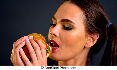 Woman eating hamburger. Girl wants to eat fast food.