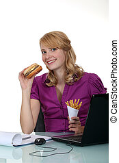 Woman eating hamburger in the office