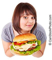 Woman eating hamburger. - Overweight woman eating hamburger...