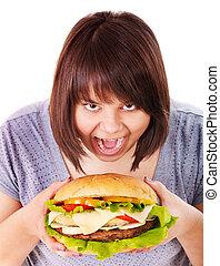 Woman eating hamburger. - Overweight woman eating hamburger....