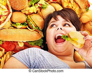 Woman eating hot dog. - Overweight woman holding hamburger.